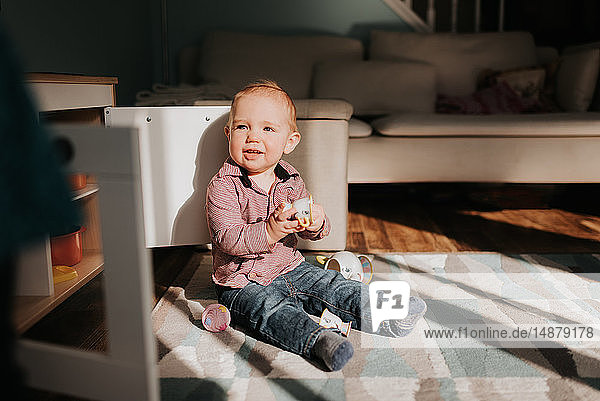 Kleiner Junge sitzt spielend auf Wohnzimmerteppich