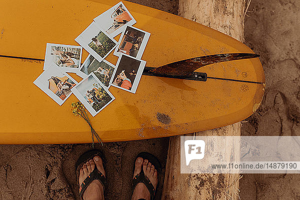 Feet of female surfer by instant photos on surfboard at beach,  Ventura,  California,  USA