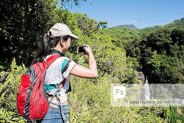 Wanderer fotografiert Wasserfall,  Waipipi Trail,  Maui,  Hawaii