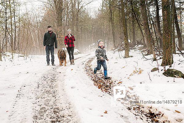 Familie mit Haushund auf Spaziergang in Schneelandschaft