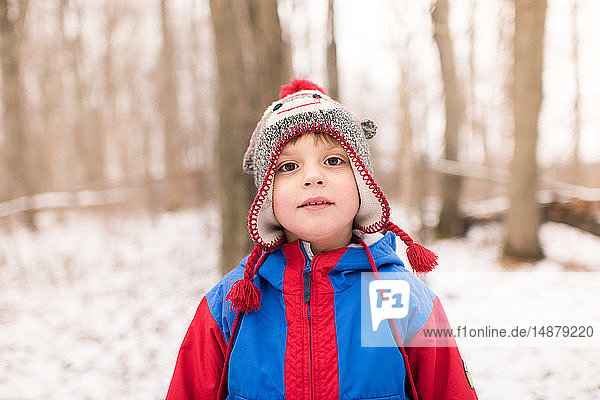 Boy in knit hat by snow covered forest  portrait