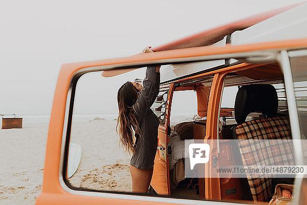 Junge Surferin entfernt Surfbrett vom Dach eines Wohnmobils am Strand  Jalama  Kalifornien  USA