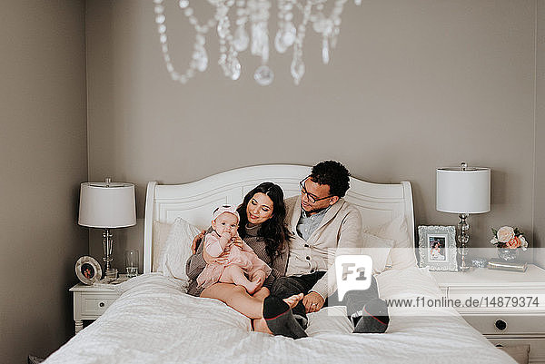 Couple with baby daughter on bed in bedroom