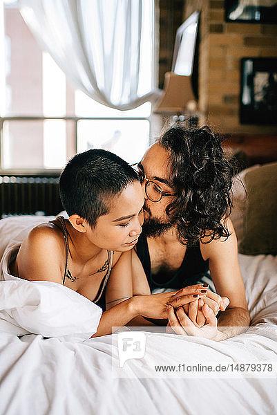 Glückliches Paar unter der Decke im Bett