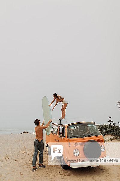 Junges surfendes Paar beim Entladen des Surfbretts vom Dach eines Wohnmobils am Strand  Jalama  Ventura  Kalifornien  USA
