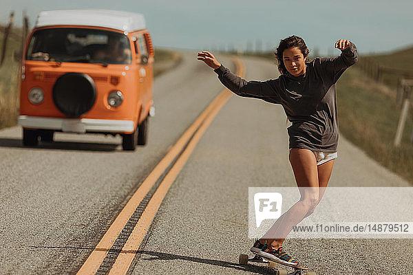 Junge Skateboardfahrerin schwenkt mit dem Skateboard die Landstrasse hinunter  gefolgt von einem Wohnmobil  Jalama  Kalifornien  USA