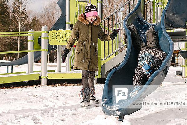 Mädchen beobachtet Bruder kopfüber auf Spielplatz  der im Schnee rutscht