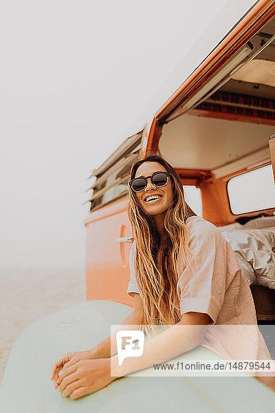 Junge Surferin sitzt auf einem Wohnmobil am Strand  Jalama  Ventura  Kalifornien  USA