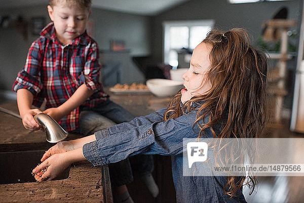 Kleinkind hilft Schwester beim Händewaschen in der Küchenspüle