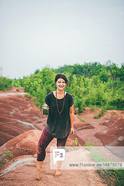 Woman drinking green juice on rock
