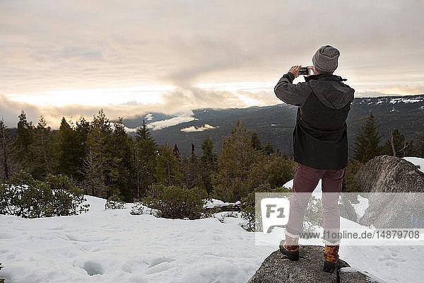 Mittelgroßer erwachsener Mann fotografiert Blick vom Fels auf schneebedeckten Berg,  Rückansicht,  Twain Harte,  Kalifornien,  USA