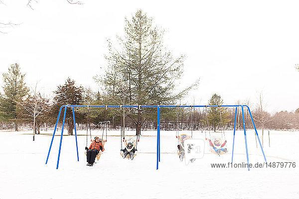 Mann und Kinder schaukeln auf einer Reihe von Spielplatzschaukeln im Schnee