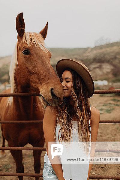 Junge Frau mit Filzhut Nase an Nase mit Pferd  Jalama  Kalifornien  USA