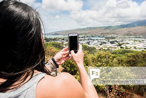 Hiker taking photograph of town of Halona Beach  Oahu  Hawaii
