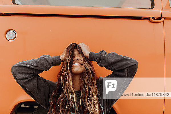 Young woman in front of orange recreational vehicle at beach  portrait  Jalama  California  USA