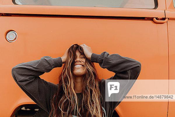 Junge Frau vor orangefarbenem Wohnmobil am Strand  Porträt  Jalama  Kalifornien  USA