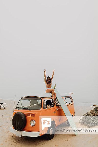Junge Surferin im Bikini macht Siegeszeichen vom Dach eines Freizeitfahrzeugs am Strand  Jalama  Kalifornien  USA
