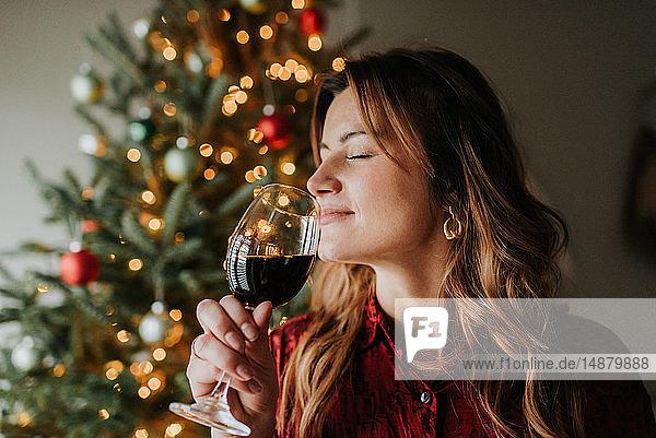 Frau riecht an einem Glas Wein neben einem geschmückten Weihnachtsbaum