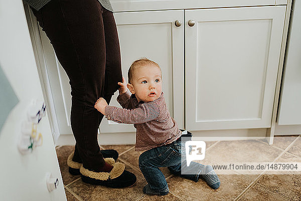 Baby boy in kitchen holding on to mother's legs