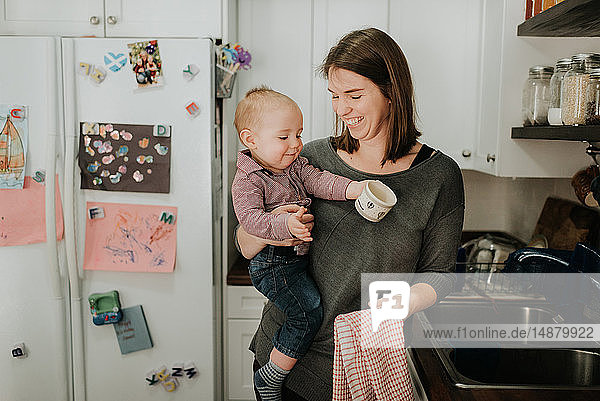 Mother carrying baby son drying dishes in kitchen