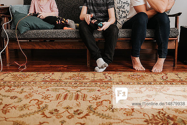 Mother sitting with children playing video game on couch