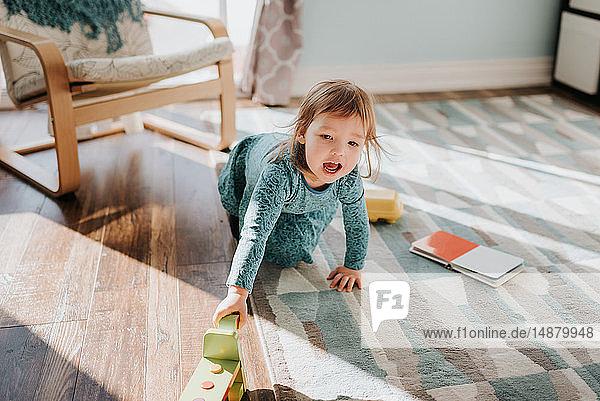 Weibliches Kleinkind spielt auf Wohnzimmerteppich