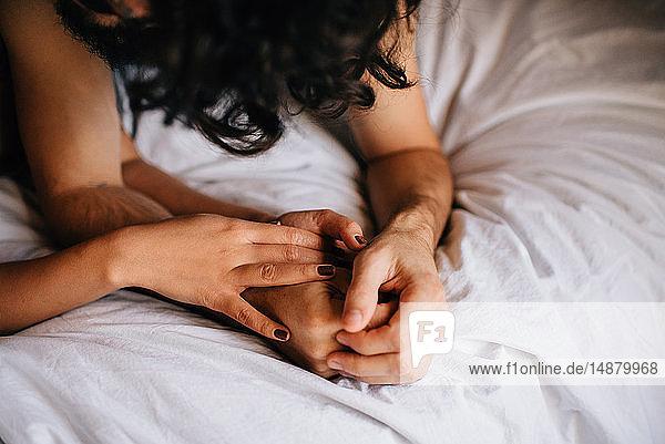 Paar  das im Bett Händchen hält