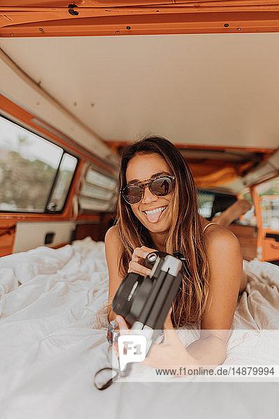 Junge Frau streckt am Strand die Zunge aus dem Heck eines Wohnmobils heraus  Portrait  Jalama  Kalifornien  USA