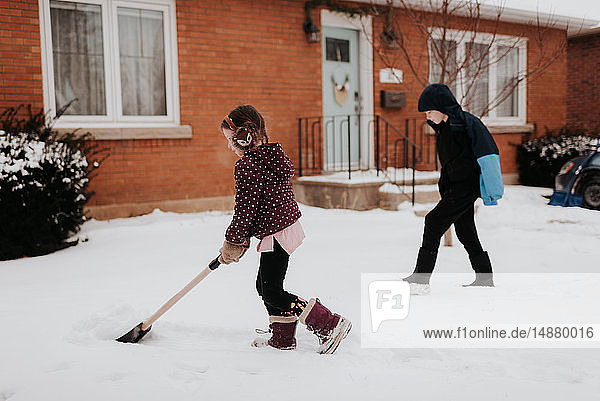 Children shovelling snow in front of house