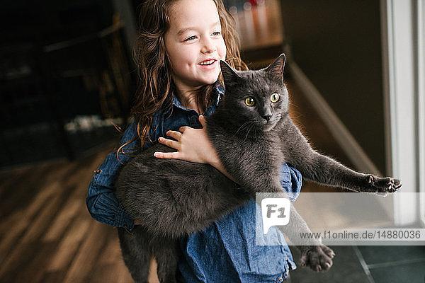 Kleines Mädchen spielt zu Hause mit Katze