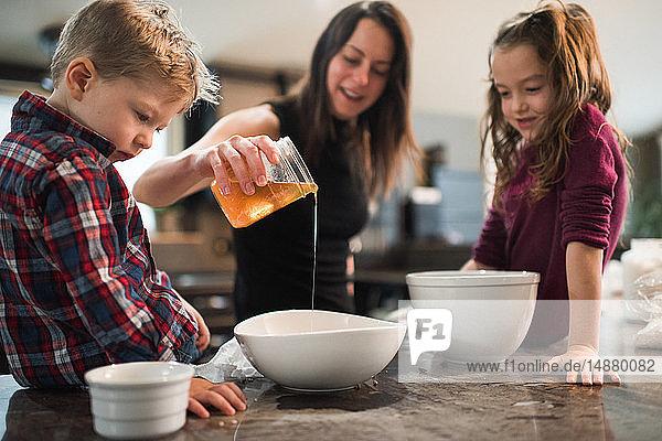 Kinder sehen zu  wie die Mutter Honig in eine Schüssel gießt