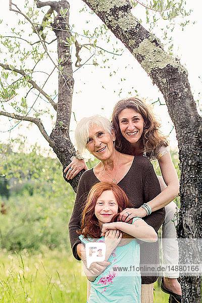 Mädchen am Gartenbaum mit Mutter und Großmutter  Porträt