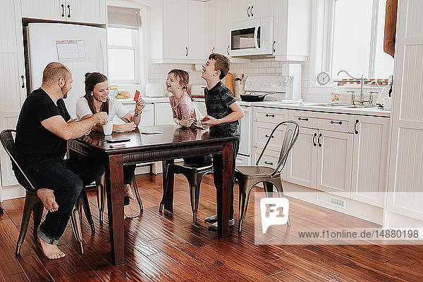 Family of four playing cards in kitchen