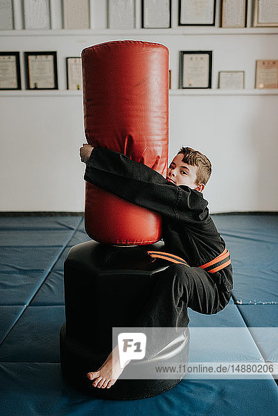 Boy clinging onto punch bag in martial arts studio