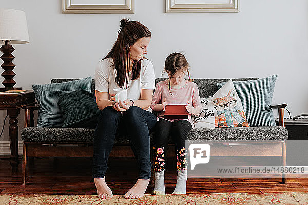 Mutter beobachtet Tochter beim Spielen auf dem Sofa