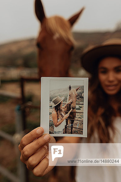 Young woman in front of horse holding up instant photo  portrait  Jalama  California  USA