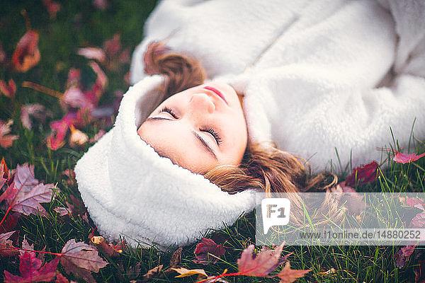 Mädchen in weißem Kapuzen-Oberteil mit geschlossenen Augen  auf Gras inmitten von Herbstlaub liegend  Bildnis