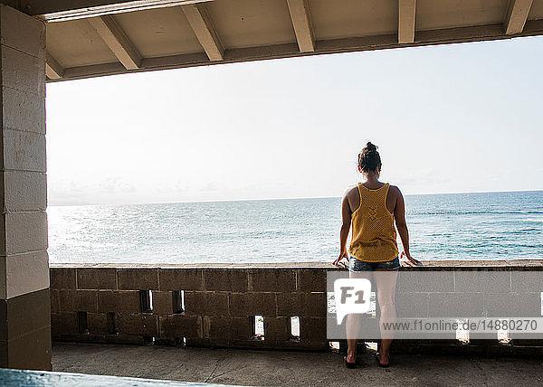 Frau schaut vom Balkon auf das Meer  Hookipa Beach  Maui  Hawaii
