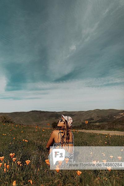 Junge Frau sitzt auf einem Feld mit Wildblumen und schaut nach oben  Jalama  Kalifornien  USA