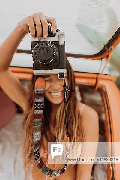 Junge Frau hält Sofortbildkamera auf dem Rücksitz eines Wohnmobils am Strand hoch  Jalama  Kalifornien  USA