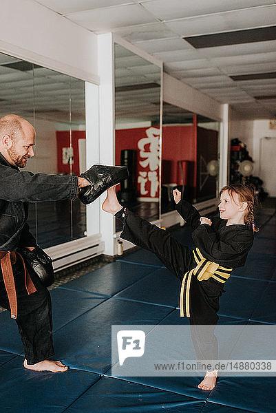 Coach and student practising kickboxing in studio
