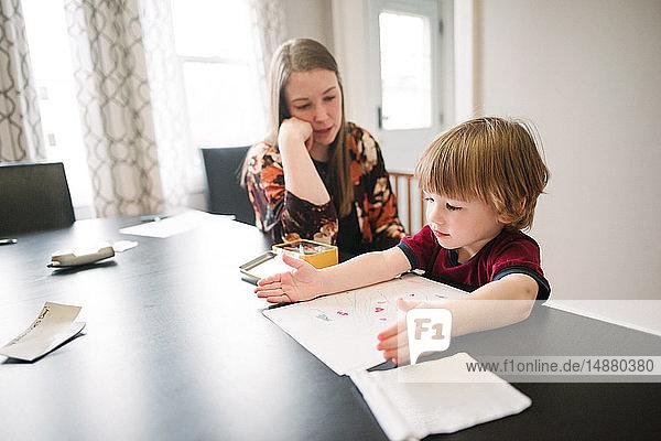 Mutter wacht über Sohn beim Lernen am Tisch