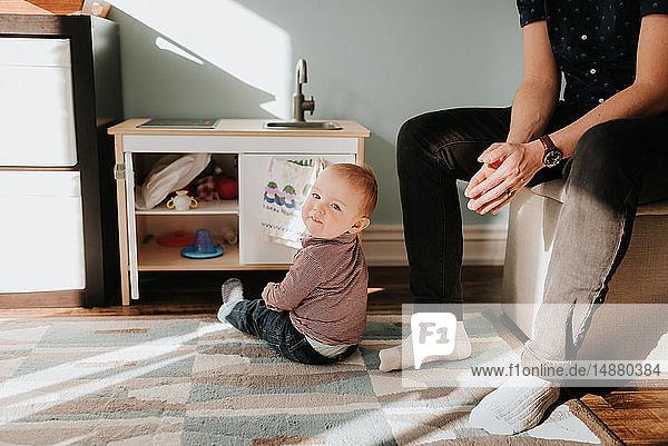 Kleiner Junge sitzt auf Wohnzimmerteppich neben dem Vater