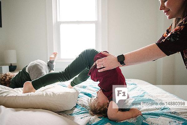 Mutter hilft Sohn beim Sturz im Bett