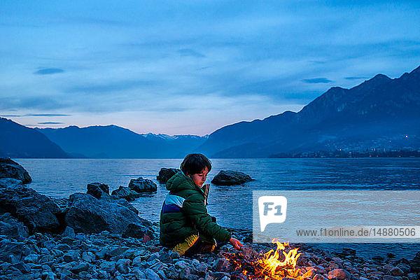 Junge am Lagerfeuer in der Abenddämmerung  Onno  Lombardei  Italien