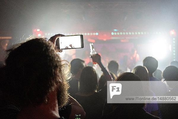 Mann fotografiert Konzert mit Smartphone
