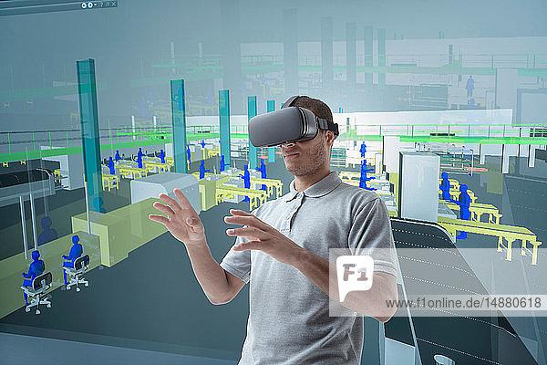 Zusammengesetztes Bild eines Ingenieurs  der ein Virtual-Reality-Headset in einer VR-Suite verwendet