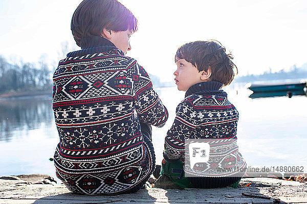 Junge und kleiner Bruder im passenden Pullover im Gespräch am Pier  Comer See  Lecco  Lombardei  Italien