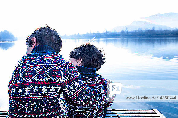 Junge und kleiner Bruder im passenden Pullover am Pier sitzend  Comer See  Lecco  Lombardei  Italien