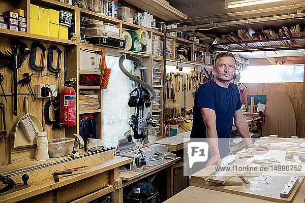 Craftsman beside his workbench and tools
